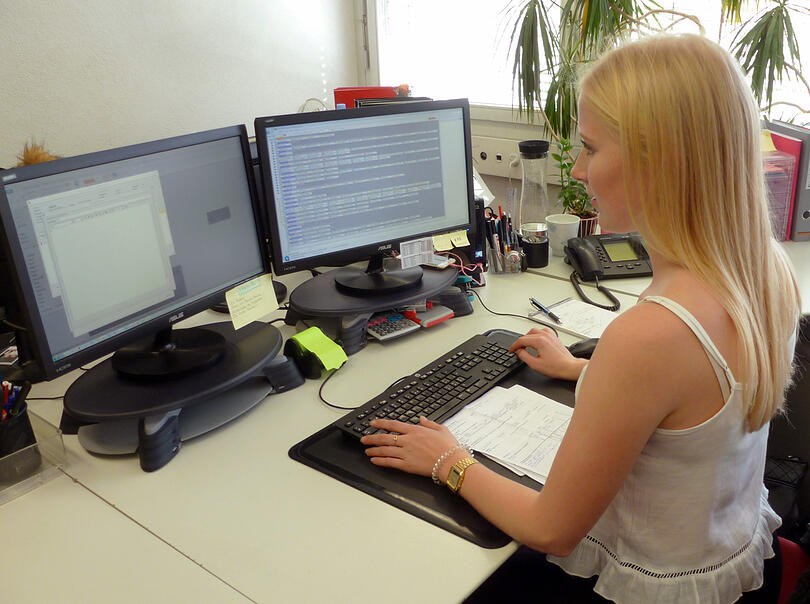 Frau sitzt am Arbeitsplatz vor zwei Bildschirmen und ist am auf der Tastatur schreiben