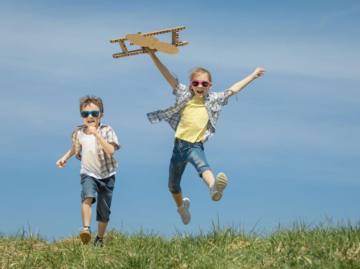 Ein Junge und ein Mädchen spielen mit einem Propellerflugzeug aus Karton